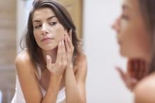 Femme examinant sa peau dans le miroir