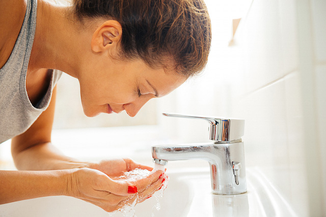 Woman washing her face with NEUTROGENA® products to help treat & prevent acne