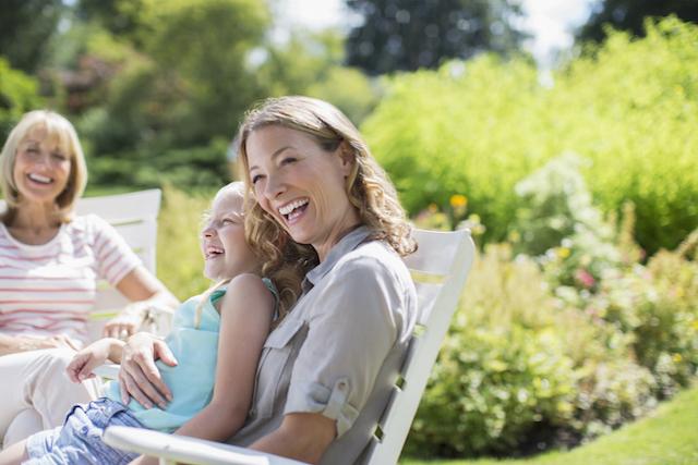 Femme souriante assise, en compagnie de sa famille, en plein air