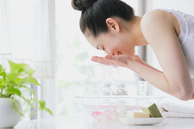 Femme aspergeant son visage d'eau après avoir utilisé un produit NEUTROGENA® pour peau sensible