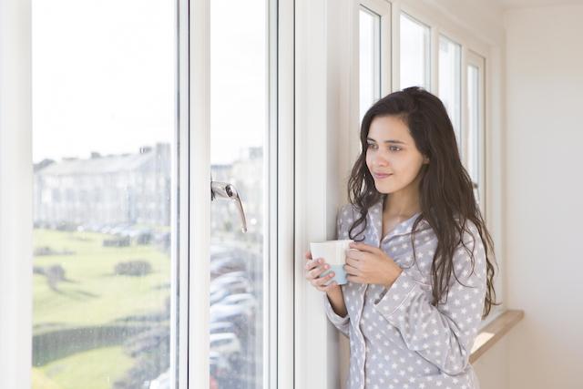 Femme debout devant une fenêtre une tasse de café à la main