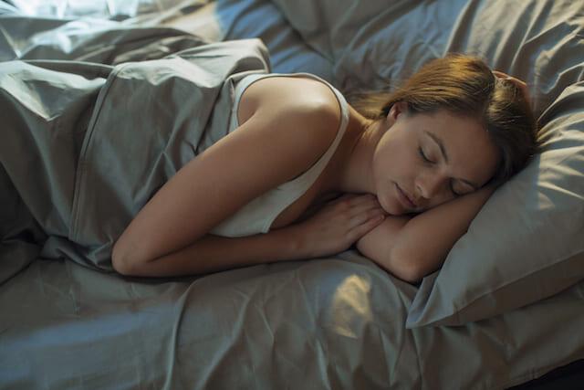 Femme dormant dans un lit après avoir appliqué un soin antiâge visage pour la nuit NEUTROGENA®