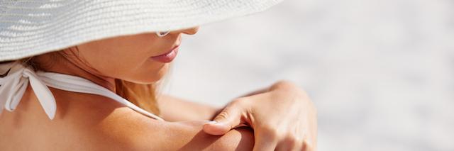 Femme appliquant un écran solaire NEUTROGENA® sur son dos