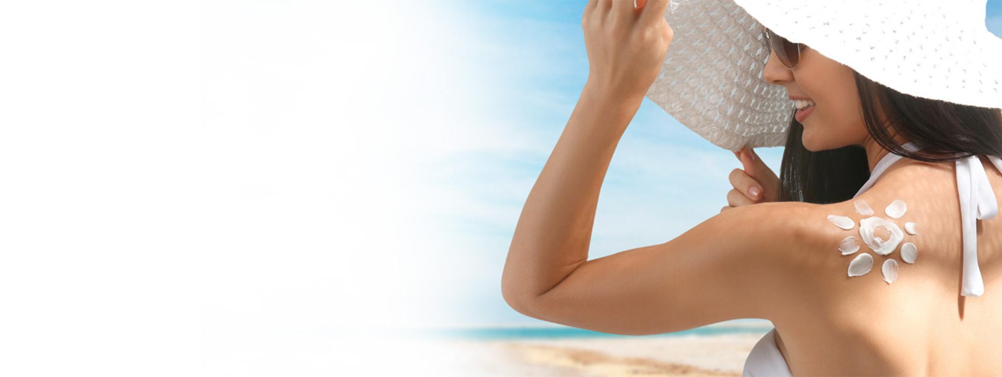 Femme avec de l'écran solaire sur l'épaule
