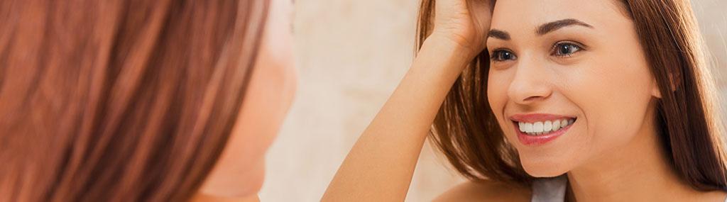 Femme qui sourit devant le miroir en voyant son teint santé