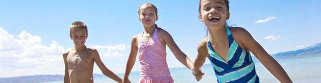Enfants ayant appliqué un écran solaire pour enfants NEUTROGENA® qui jouent au bord de l'eau