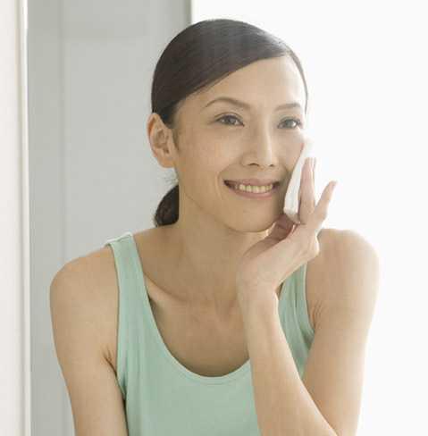 Femme souriant pendant qu'elle applique un produit antiâge NEUTROGENA® avec un coton