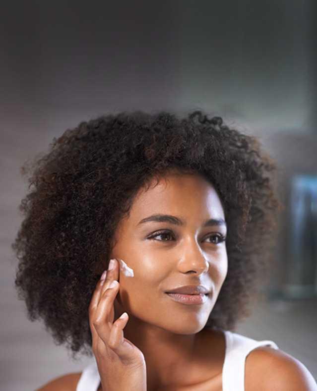 Woman applying NEUTROGENA® moisturizer
