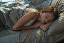 Femme qui dort dans son lit après avoir appliqué un soin de la peau antiâge pour la nuit NEUTROGENA® sur son visage