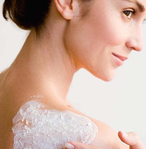 Femme appliquant un exfoliant pour le corps NEUTROGENA® sur son épaule