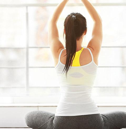 Femme vêtue d'un haut blanc et de pantalons noirs faisant du yoga pour une vie saine